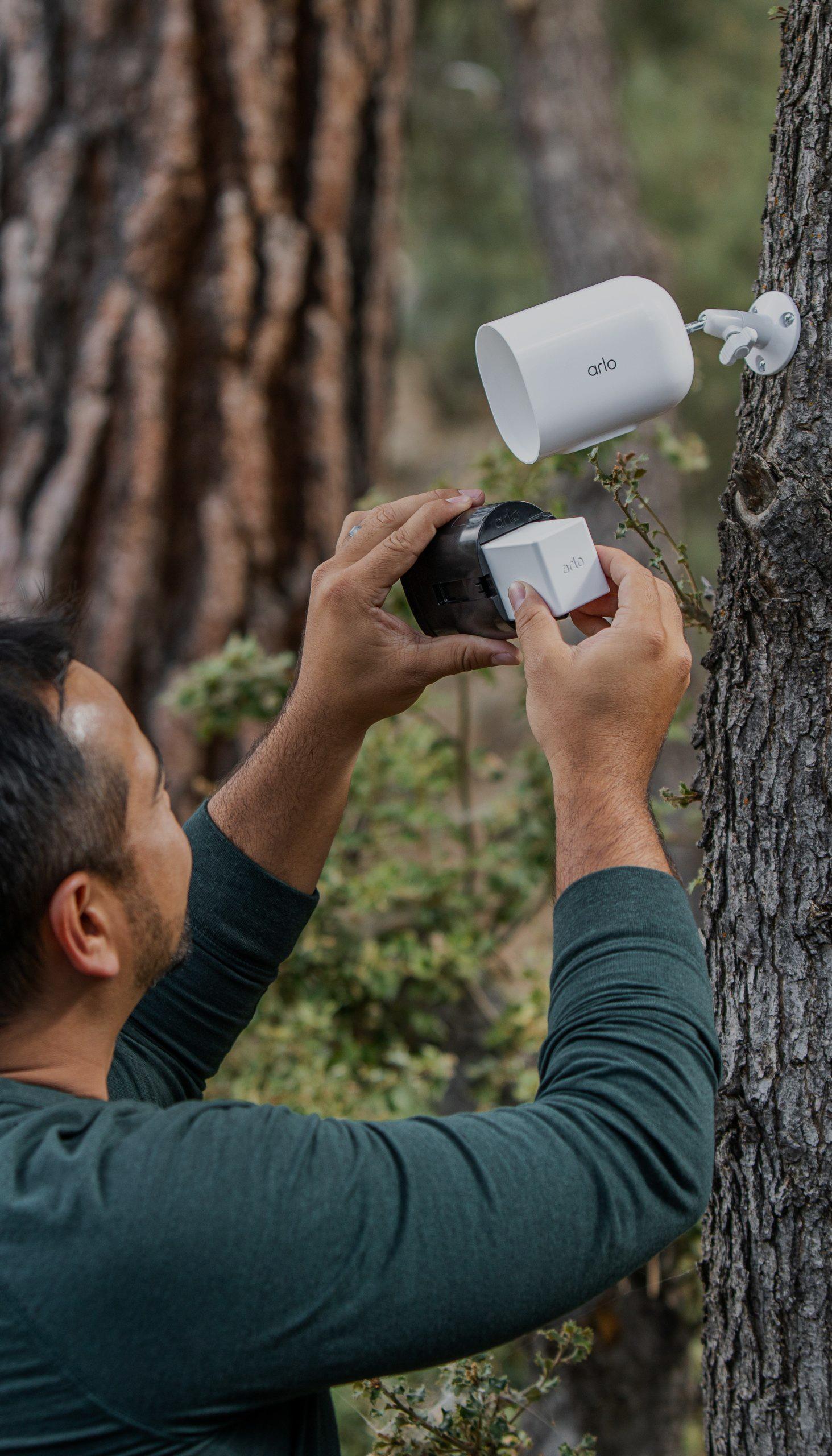 man hiding Arlo outdoor camera